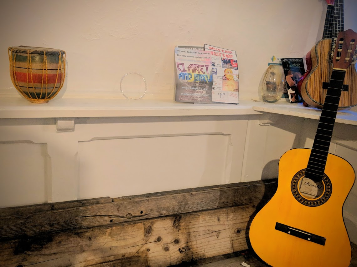 Propped up against one of the workbenches is one of the many guitars scattered around the Shift Cafe