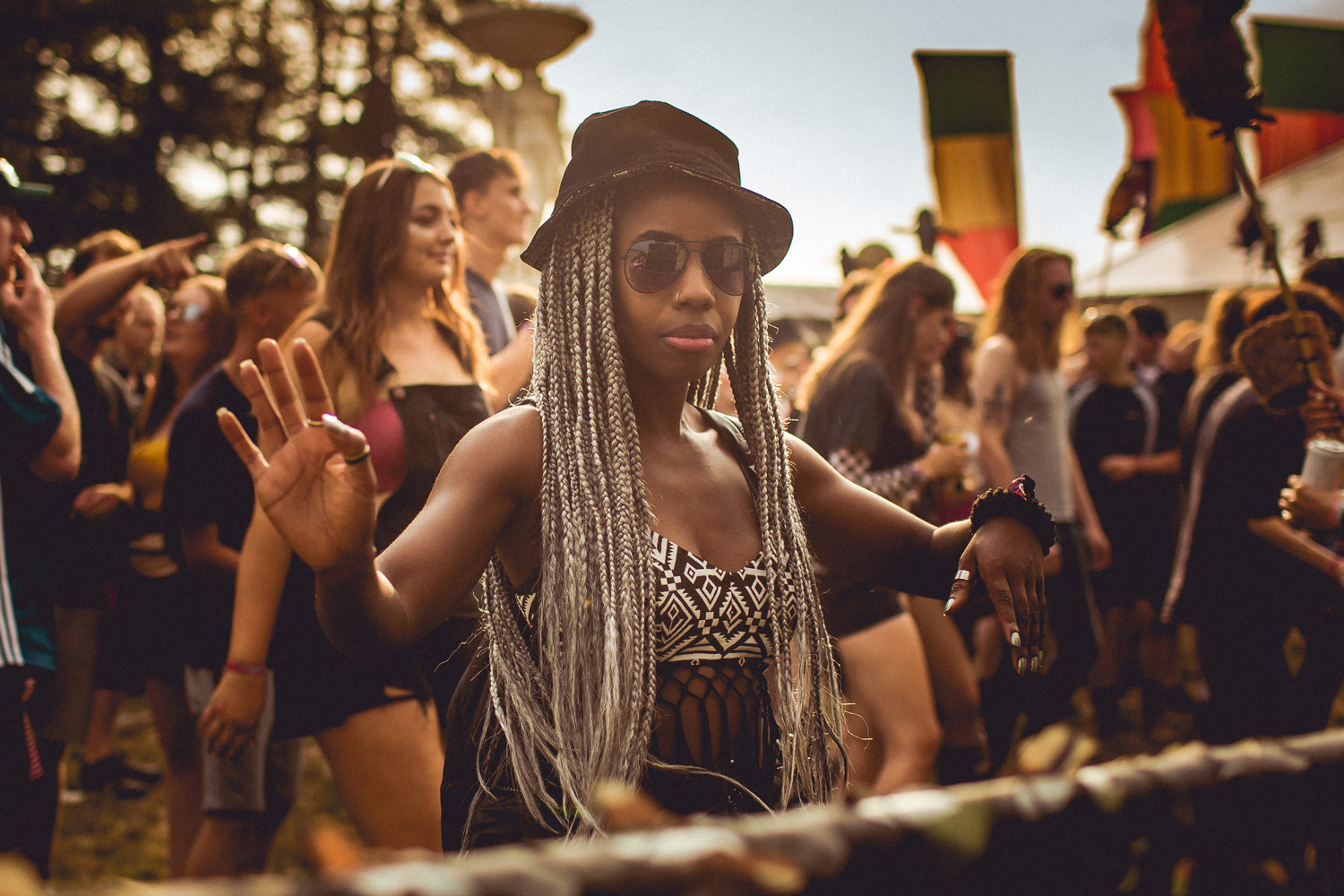 Festival go-er in bucket hat, sunglasses and long white-blonde braids dancing at sunset.