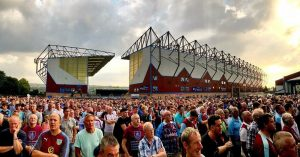 Large crowd of people with Turf Moor in the background